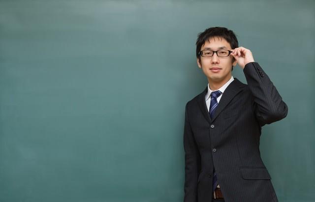 メガネをかけた塾の講師と黒板の写真