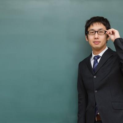 「メガネをかけた塾の講師と黒板」の写真素材