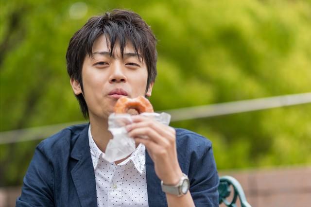 笑顔でドーナツを食べるWebデザイナーの写真