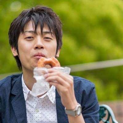 「ドーナッツを食べるWebデザイナー」の写真素材