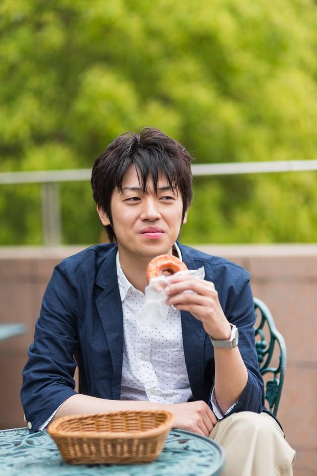 テーブルでドーナツを食べる男性の写真