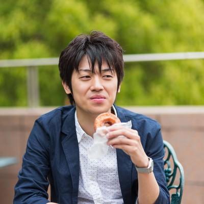 「テーブルでドーナツを食べる男性」の写真素材