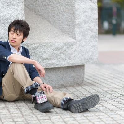 「膝を立てて座る青年」の写真素材