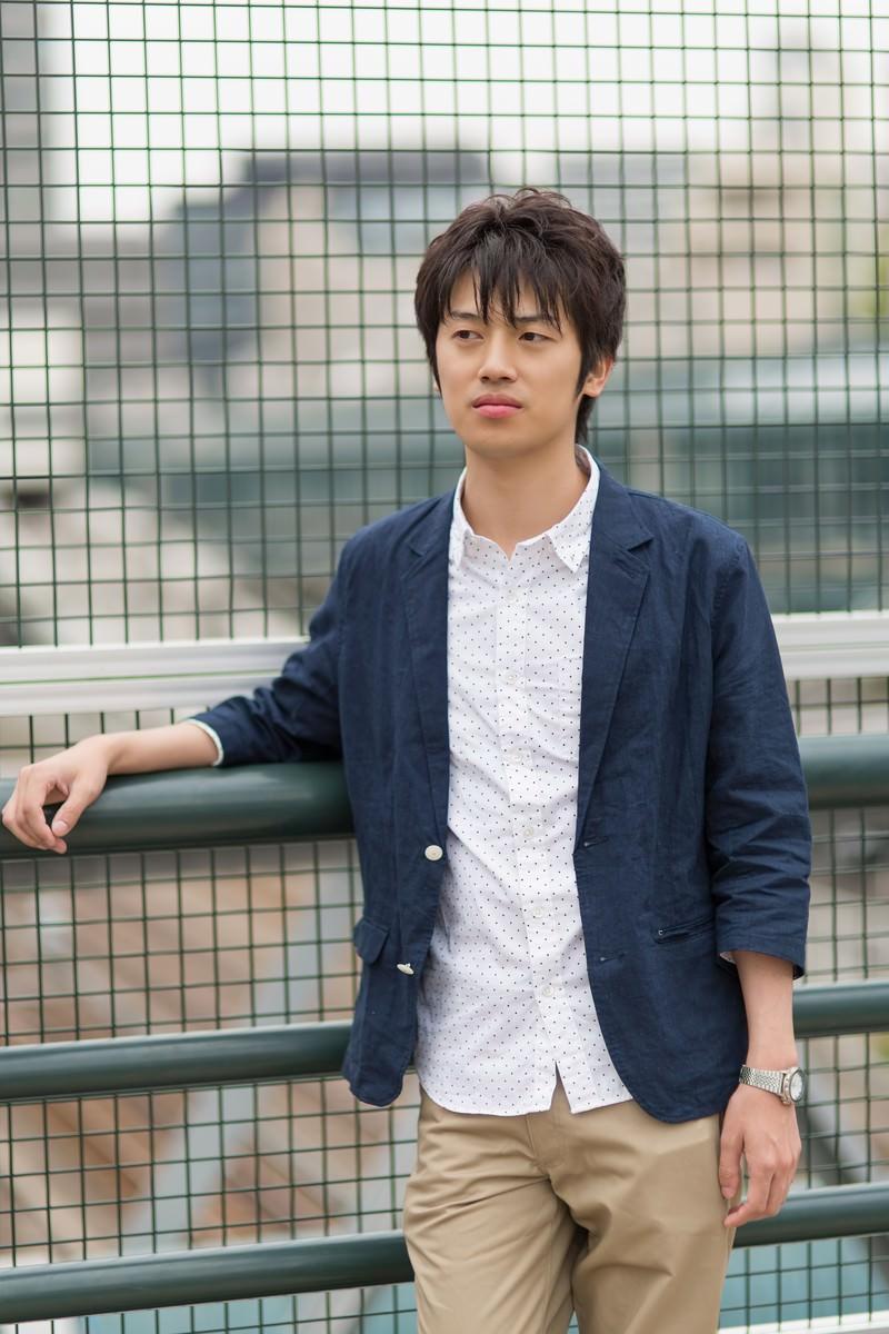 「金網に寄りかかりポーズをとる男性」の写真[モデル:Tsuyoshi.]