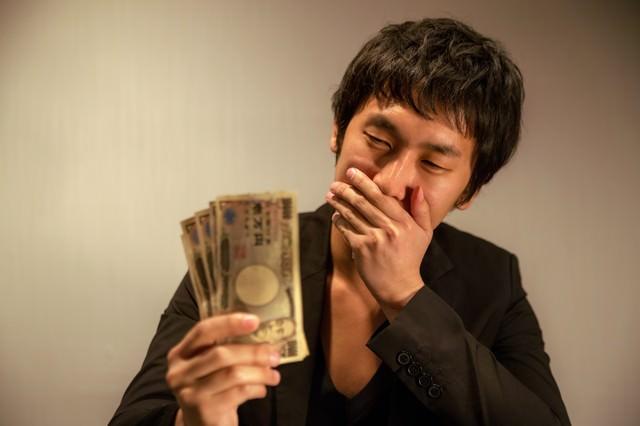 報酬を手に入れ、「うわっ・・・こんなに!」と口に手を当て驚く男性の写真
