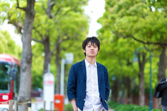 緑の道を歩く青年の写真