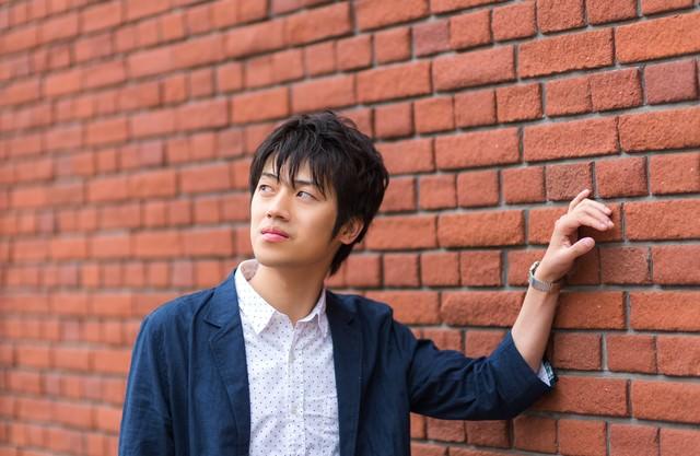 レンガの壁に寄りかかる青年の写真