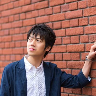 「レンガの壁に寄りかかる青年」の写真素材