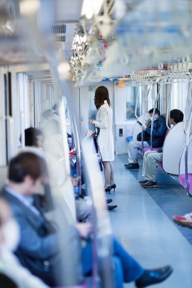 電車に乗るハイヒールの女性の写真