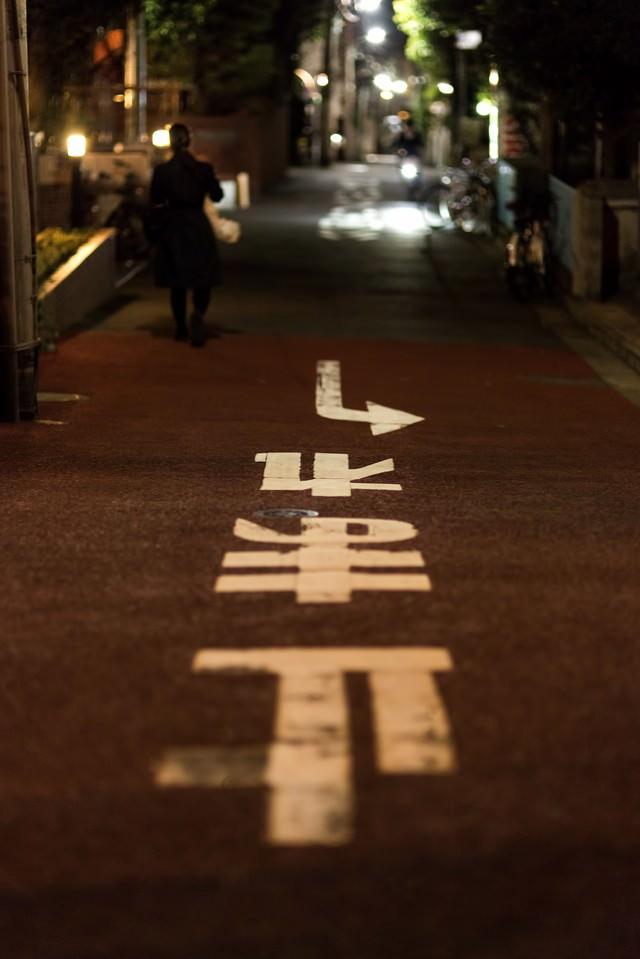 止まれの道路標示と路地裏の写真