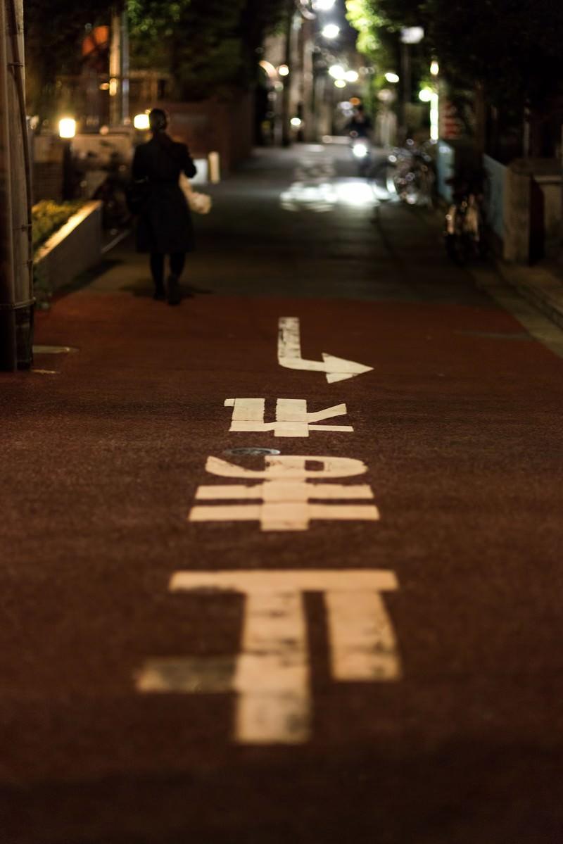 「止まれの道路標示と路地裏」の写真