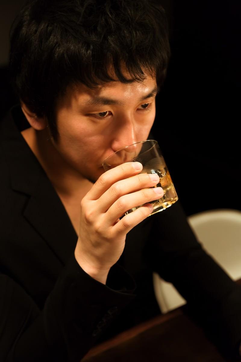 「ウィスキーを口にする男性」の写真[モデル:大川竜弥]