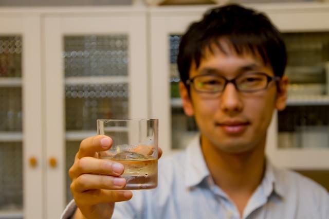 グラスを持って乾杯する男性の写真