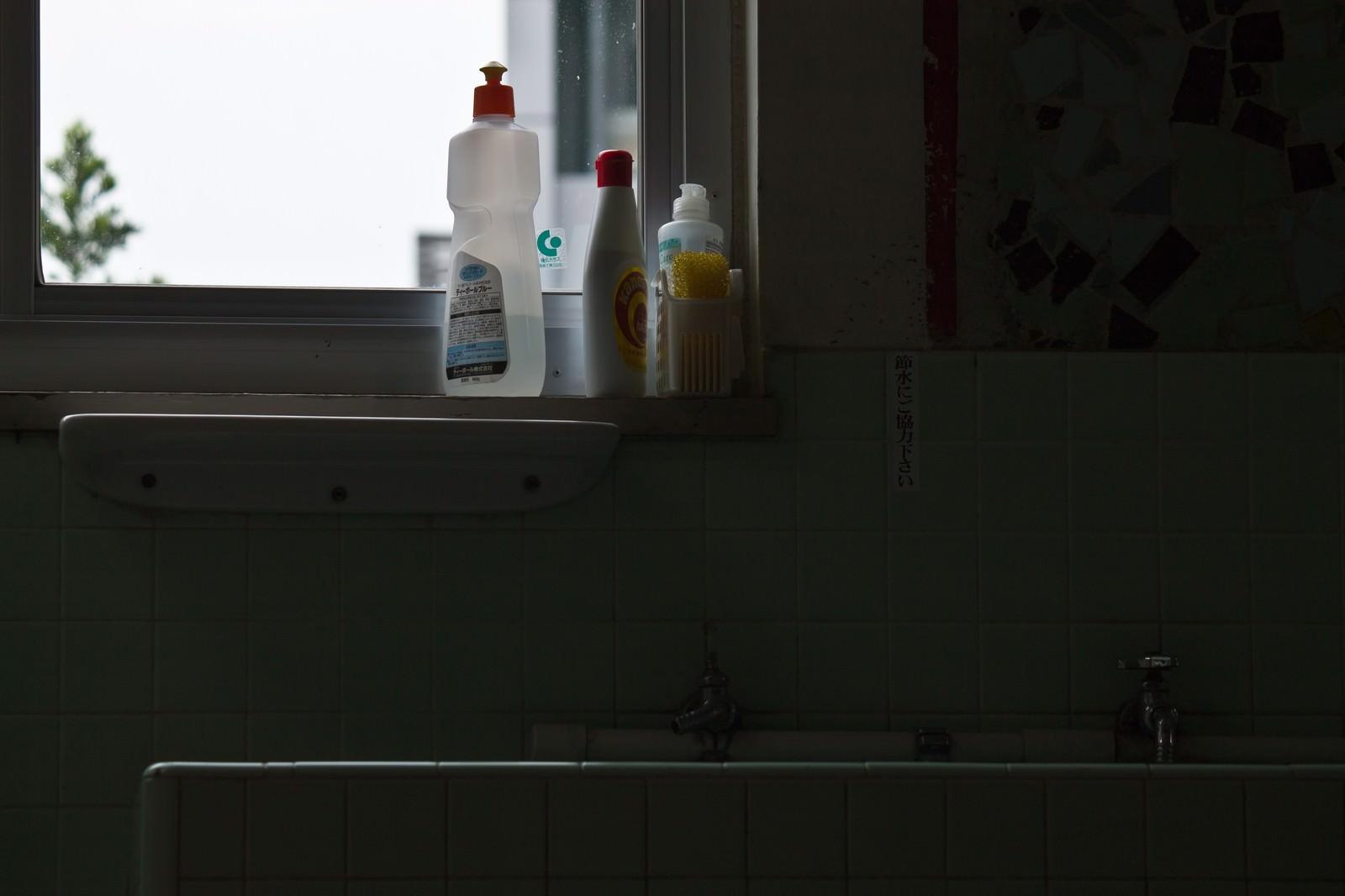 「窓際に並ぶ洗剤とタイルの蛇口」の写真