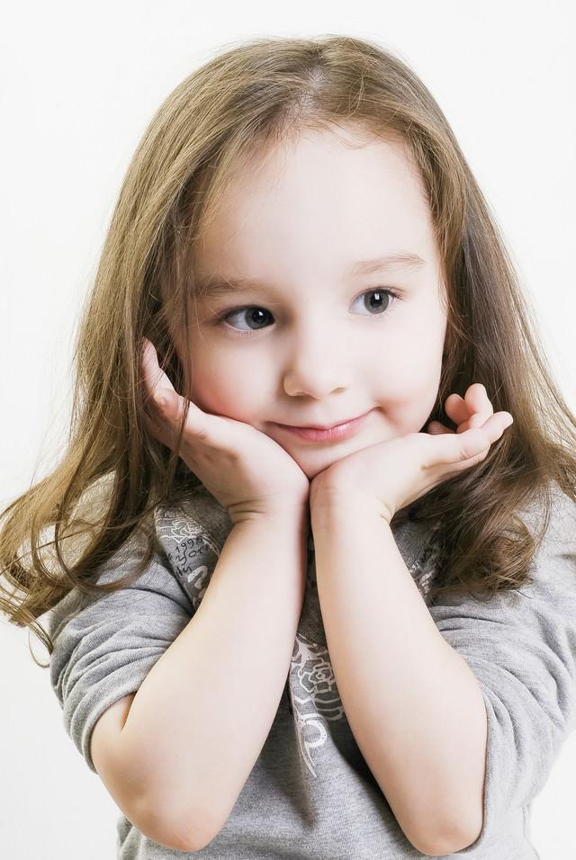 両手に顎を乗せて微笑む幼い女の子の写真