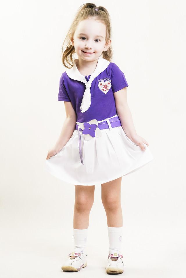 スカートの裾を両手で摘みながら笑顔でポーズをきめる女の子の写真