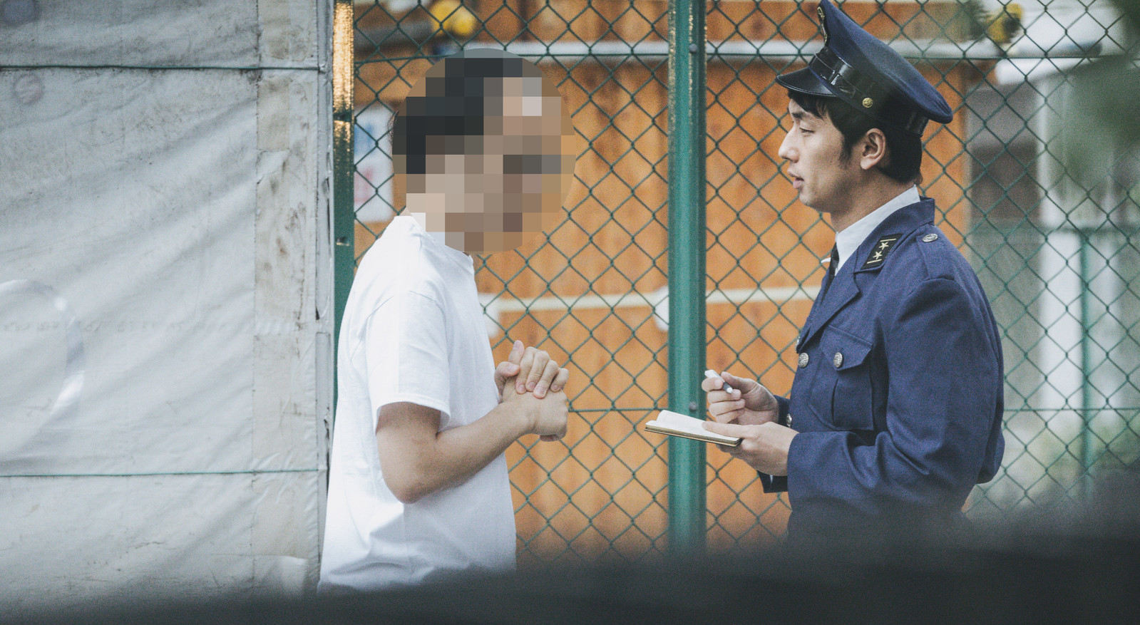 「挙動不審な男性に声をかける警察官」の写真[モデル:大川竜弥]