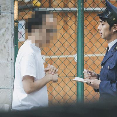 挙動不審な男性に声をかける警察官の写真