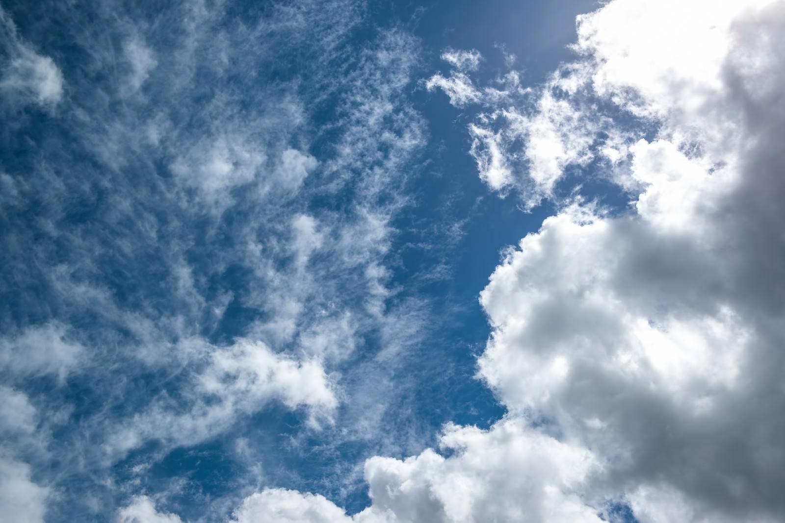 「昼の太陽と青い空、雲」の写真