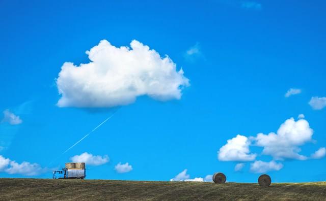 青空の下、トラックと牧草ロールの写真