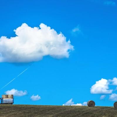 「青空の下、トラックと牧草ロール」の写真素材