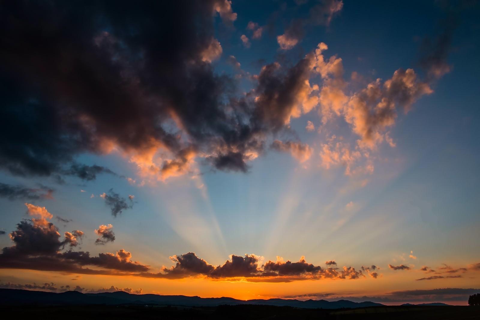 「夕暮れの空と伸びた光」の写真