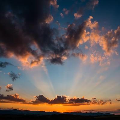 夕暮れの空と伸びた光の写真