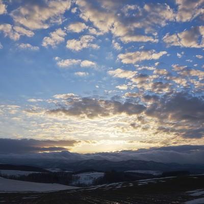 「雪解け丘の夕暮れ」の写真素材