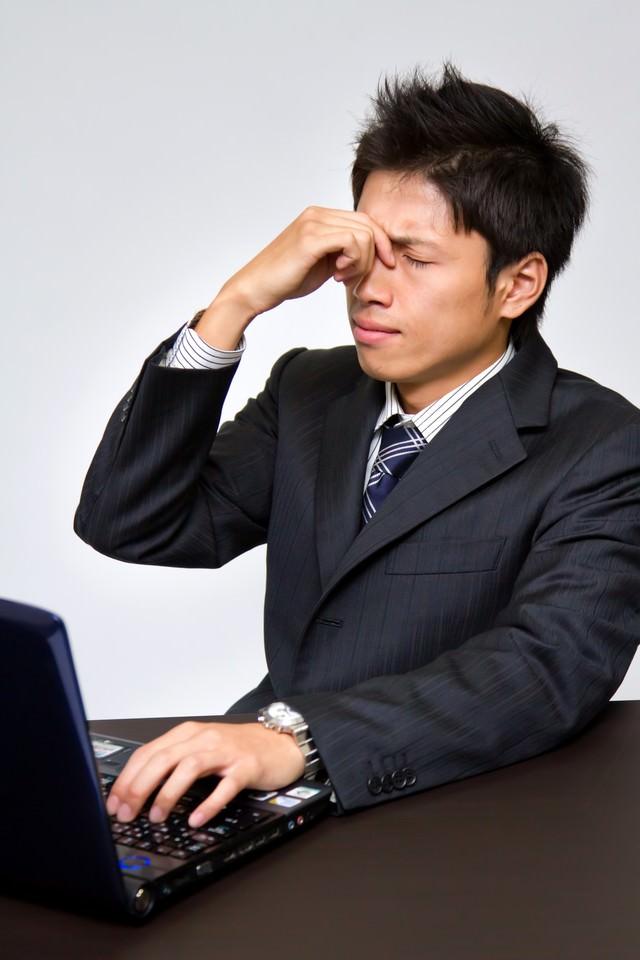 PCのやり過ぎで目が疲れるビジネスマンの写真