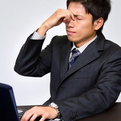 「PCのやり過ぎで目が疲れるビジネスマン」の写真素材