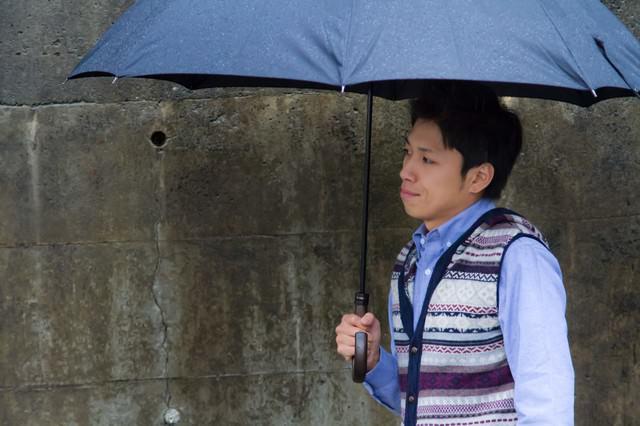 雨の日に傘を差して恋人を待つ男性の写真