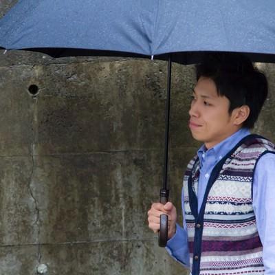 「雨の日に傘を差して恋人を待つ男性」の写真素材