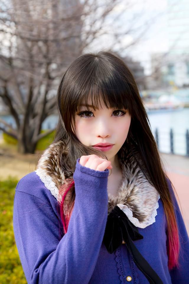 冬の街道でこちらを見つめる女性の写真