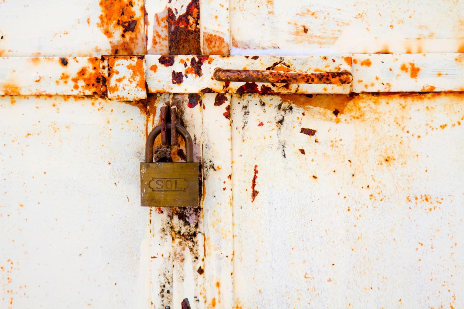 「決して開かない錆びた扉と南京錠」の写真