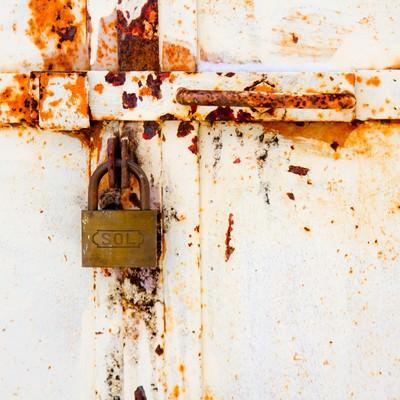 決して開かない錆びた扉と南京錠の写真