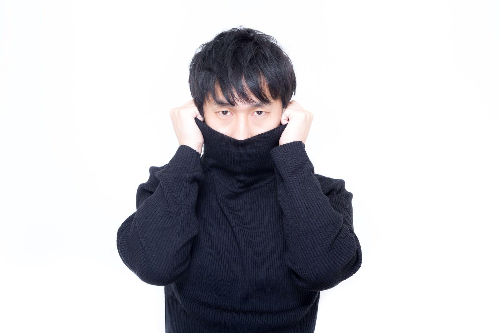 「寒さに震えタートルネックで首元を隠す男性」の写真[モデル:大川竜弥]