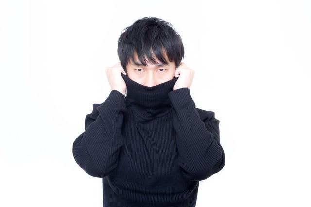 寒さに震えタートルネックで首元を隠す男性の写真