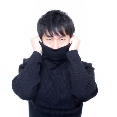 「寒さに震えタートルネックで首元を隠す男性」の写真素材
