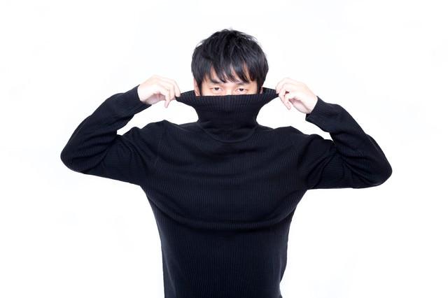 髪型が崩れないように慎重にタートルネックを着るオシャメンの写真