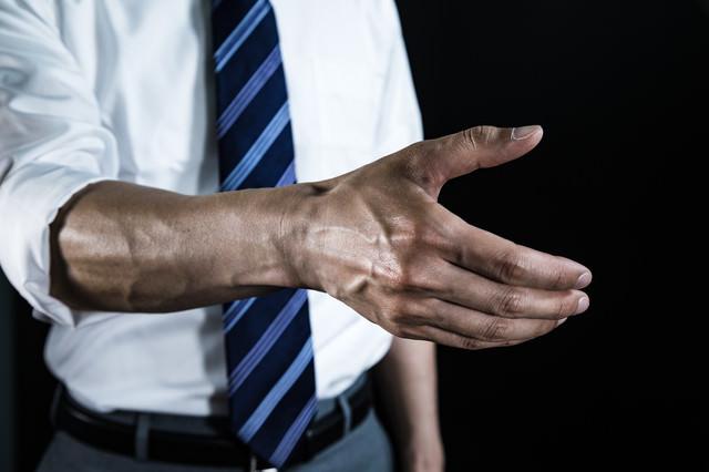腕まくりして血管を強調した上で握手を求める会社員の写真