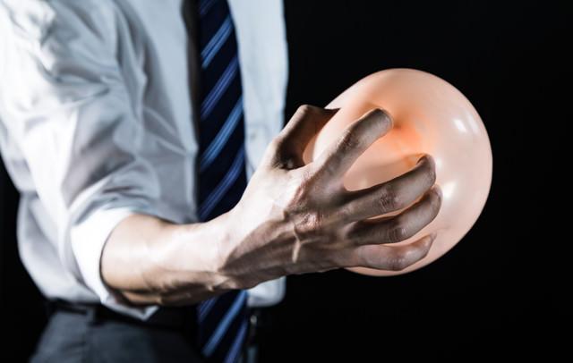 手から気功弾を発する会社員の写真
