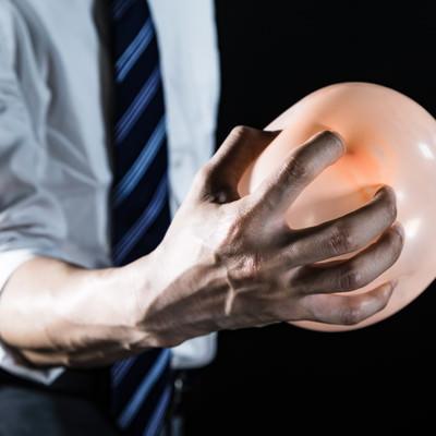 「手から気功弾を発する会社員」の写真素材