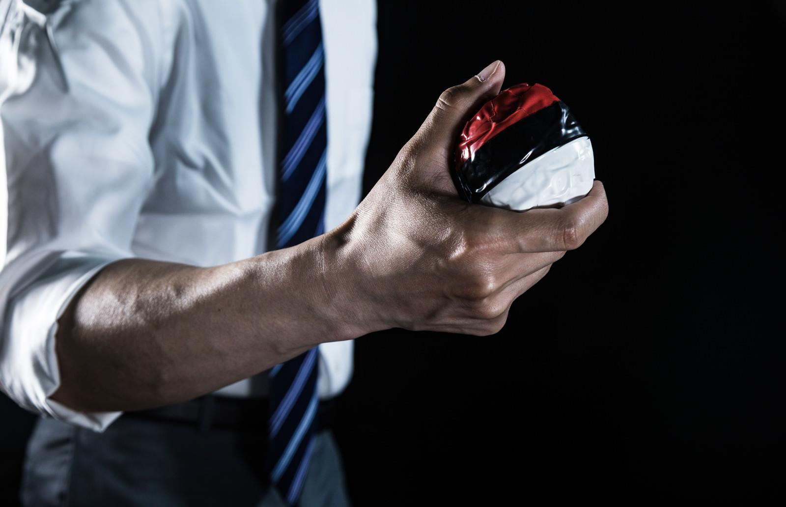 「紅白ボールを握りしめる会社員ゲーマー」の写真[モデル:大川竜弥]
