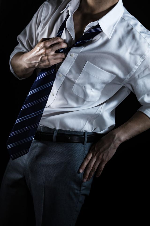 ネクタイを緩めるスーツ姿の男性(クールビズ)
