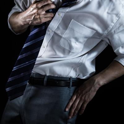 ネクタイを緩めるスーツ姿の男性(クールビズ)の写真