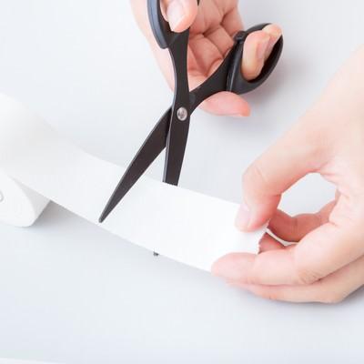 ホワイトテープをハサミでカットするの写真