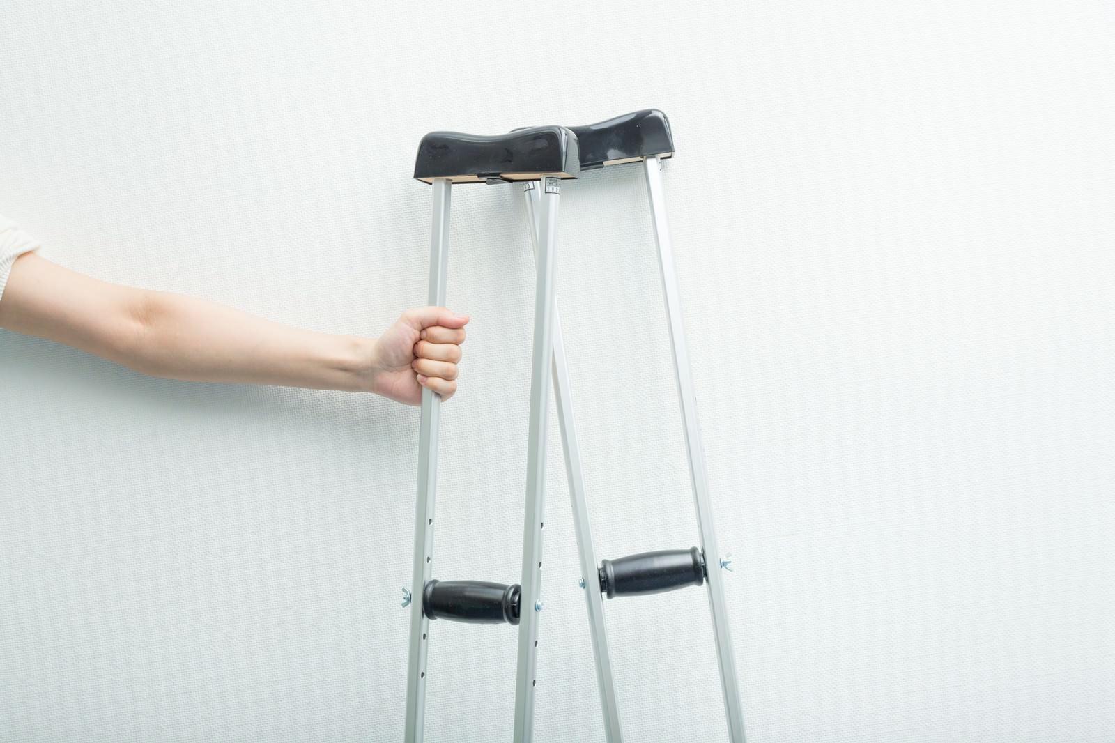 「松葉杖を握りしめる男性の手」の写真