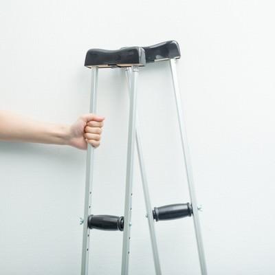 松葉杖を握りしめる男性の手の写真