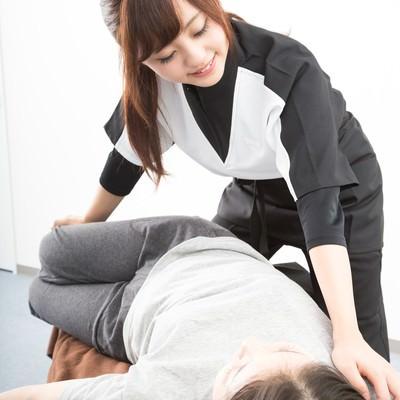 「整体を行う若い女性スタッフ」の写真素材