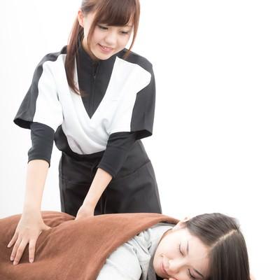 「背中を施術する女性スタッフ」の写真素材